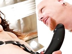 She is wearing a monstrous black strap-on and is measuring it to his cock